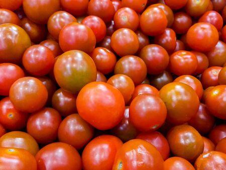 Pile of fresh  raw  cherry tomatos  for sale.