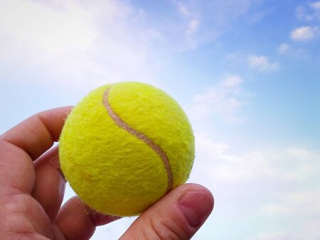 Close-up of  tennis ball in a man  hand agains blue sky