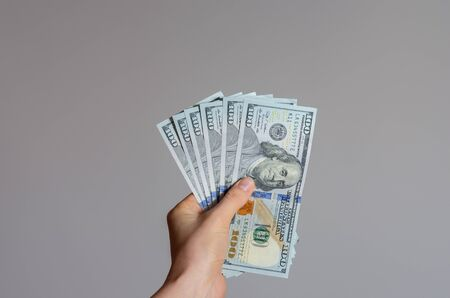 Close up view of a woman's hand holding a pile of 100 dollar banknotes   money on a gray background . The economic impact of coronavirus  in  United state of  America . Imagens