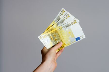 Close up view of a woman's hand holding a pile of euro banknotes   money on a gray background . The economic impact of coronavirus  in  European Union . Imagens