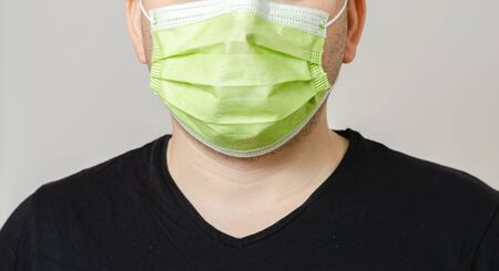 Young  man with a surgical  mask on his face protecting himself from the transmission of diseases and covid-19.