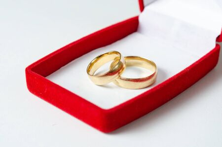 Close-up view of husband and wife  wedding rings in red gift  box isolated on a white background .