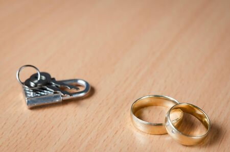 Close up view of a padlock with key  next to two wedding rings representing a concept of united marriage without secrets and trust .