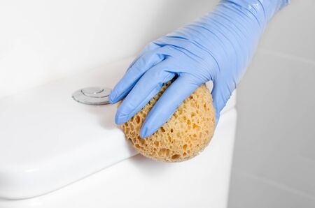 Maid with surgical gloves cleaning flush toilet with disinfectant wet wipes. Bacteria and coronavirus spreading prevention .