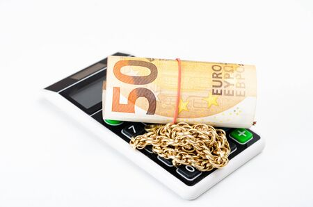 Close-up o f 50 euro banknote    and  gold chain  on a pocket calculator  representing concept  of budget of the European Union during the crisis code-19 .European policies during the coronavirus crisis . Imagens