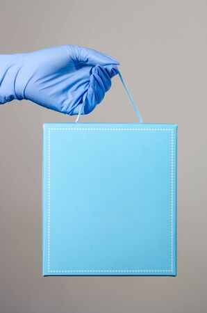 Hand with surgical gloves of a woman or man holding a blue giftbox package . Protective measures for the distribution of parcels during the covid-19 pandemic .