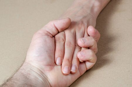 Close-up  hand  of a woman and a man holding each other tightly . Banco de Imagens - 147989232