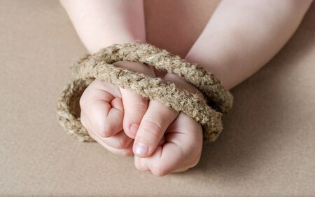 Child hands tied with a rope .Concept regarding slavery .