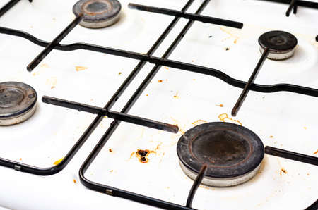 Close up view of a stove dirty with food and grease.