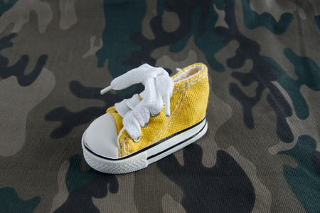 camo: Yellow sneaker on camo fabric