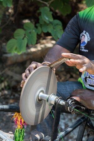an Indian man holding a knife in his hand to sharpen it on the rotating whetstone which is connected to the rear wheel of his bicycle through a string