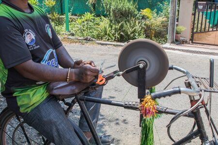an Indian man sharpening a steel scissor on the rotating whetstone which is mounted on his bicycle while seating on the carrier