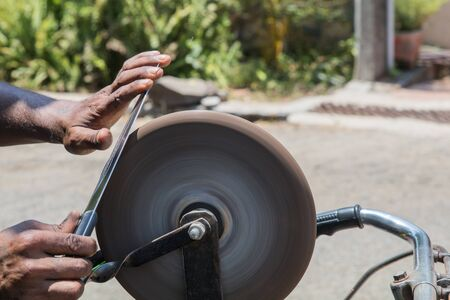 an Indian man sharpening a kitchen knife on the rotating whetstone which is connected to the rear wheel of his bicycle through a string Reklamní fotografie