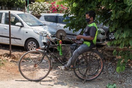 an Indian man sharpening tools on the rotating whetstone which is connected to the rear wheel of his bicycle through a string while seating on the carrier Reklamní fotografie