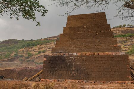 a brick kiln from a remote village in India. Raw bricks arranged in stepped pyramid form and set on fire to produce bricks for construction.