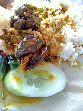 nasi bungkus (mix rice) indonesian cuisine food. rice with fried chicken heart and lungs, chili sauce (sambal), cucumber and lemon basil. the cheapest indonesian food from traditional restaurant.