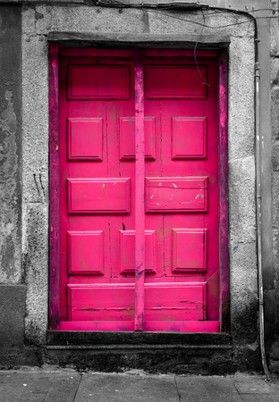 unoccupied: A pink door at the tourist street in Porto, Portugal. The surrounding walls and the porch are desaturated. Stock Photo
