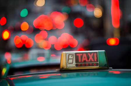 under the influence: Close up of the taxi sign with the red lights bokeh in Porto, Portugal