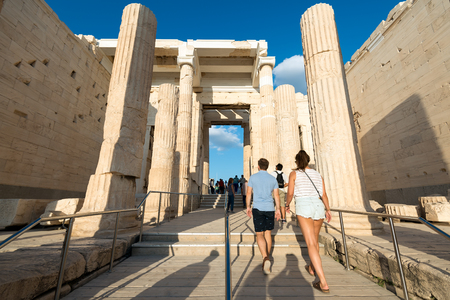 appraise: Athens, Greece - August 28, 2016: Visitors at the main entrance to Acropolis of Athens. You can appraise the dimensions of the old building.