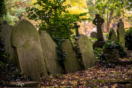 Leaned old tombstones at the Highgate Cemetery, London famous for Karl Marx grave
