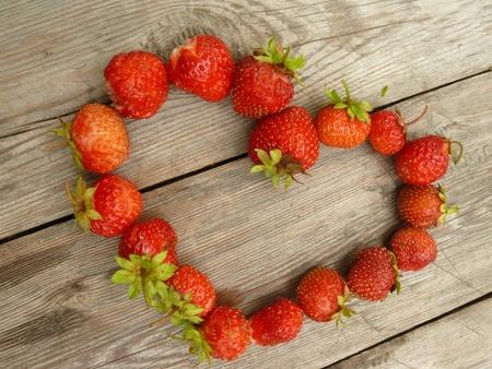 p�rim�tre: Coeur fait de la fraise juteuse couch� sur une table en bois Banque d'images