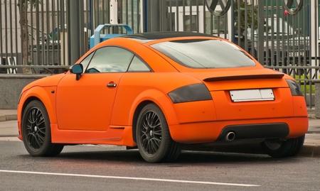 Bright Orange  subcompact car in the street, brand Audi  photo