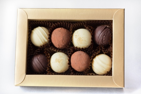 A golden box with eight assorted chocolates Stock Photo