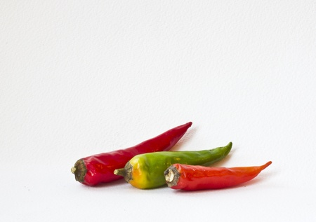 Three chili peppers lying on white background photo