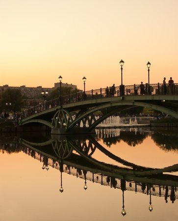 Reflection of the bridge in calm water of the lake at sunset  photo