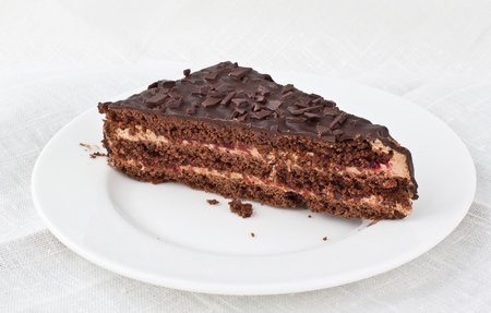 piece of chocolate cake with cherry jam lying on white plate with white linen background  photo
