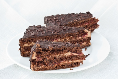 three cornered: 3 pieces of chocolate cake with cherry jam lying on white plate with white linen background  Stock Photo