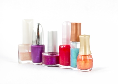six colorful bottles of nail polish on white background with shallow depth of field photo