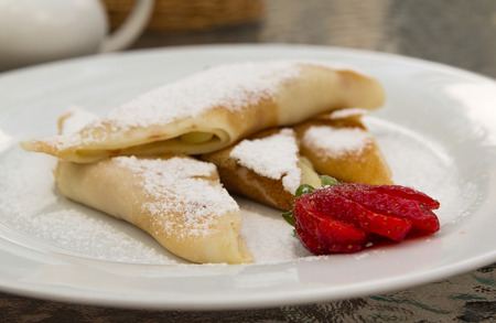 high calorie: Sweet breakfast - pancakes with strawberry and powder on a white plate. Close-up view