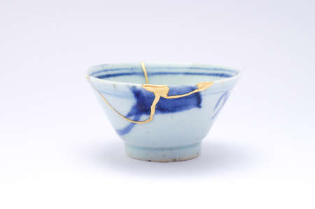 Kintsugi sake cup. Gold cracks restoration on old Japanese pottery restored with the antique restoration technique The unique beauty of imperfections.