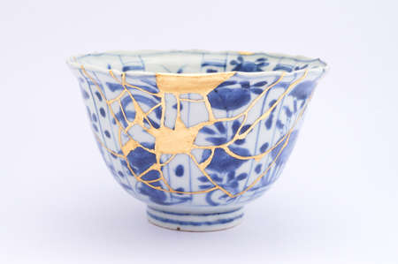 Kintsugi tea ceremony bowl. Gold cracks restoration on old Japanese pottery restored with the antique restoration technique The unique beauty of imperfections.
