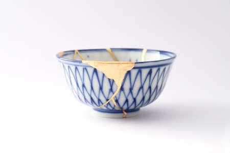 Kintsugi pottery. Gold cracks restoration on old Japanese pottery restored with the antique Kintsugi restoration technique. The beauty of imperfections.