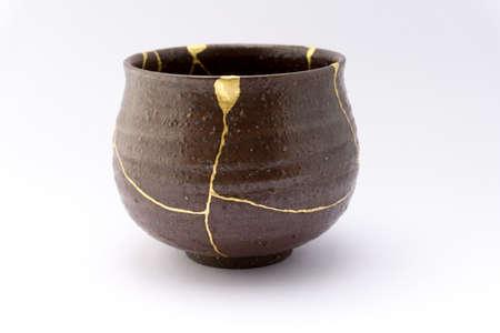 Kintsugi Japanese tea ceremony bowl. Gold cracks restoration on old Japanese pottery restored with the antique Kintsugi restoration technique. The beauty of imperfections.