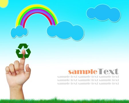 hand touching on the grass with a blue sky and rainbow  Stock Photo