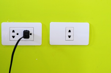 black cable plugged in a white electric outlet mounted on green wall photo