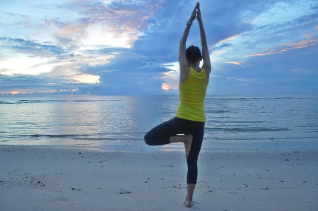 Beautiful young woman making Yoga exercises on the beach  photo