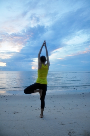 Beautiful young woman making Yoga exercises on the beach Stock Photo