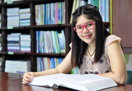 Smiling student sitting at a desk in a library while reading notes Stock Photo
