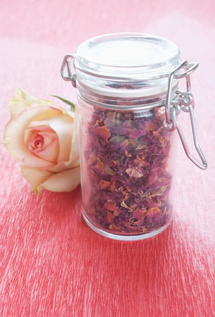 Dried rose petals in a jar with rose photo