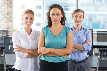 earing: Group of three young businesswomen standing and smiling with office interior in background Stock Photo