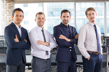 confidently: Group of four successful businessmen standing side by side in office, looking at camera confidently. Teamwork concept Stock Photo