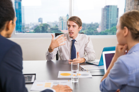 emotionally: Young business leader explaining emotionally business issues to his team at meeting in office