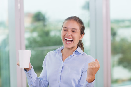 close fist: Close up portrait of cheering young businesswoman closing her eyes, pumping her fist and holding cup with window and blurry city view outside in background.