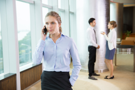 Young businesswoman talking on mobile phone and standing near window in office with male and female colleagues standing in background and discussing issues.
