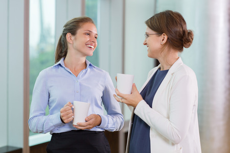 Two young businesswomen holding cups, standing, smiling and talking with office window in background 版權商用圖片