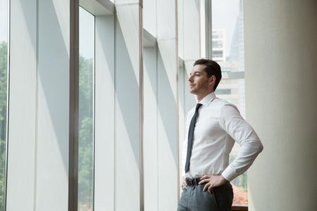 Jonge zakenman glimlachen en staan met de handen op de heupen en op zoek via het kantoor raam met wazige uitzicht op de stad buiten